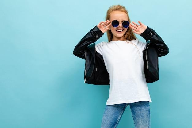Elegante chica europea en gafas de sol con una camiseta sin mangas con maqueta en azul claro