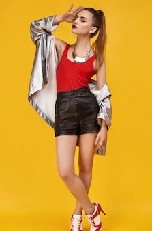 Elegante chica glamour hipster en top rojo, shorts negros y chaqueta vaquera