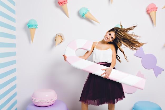 Elegante chica golosa sonriente pasar tiempo en la fiesta de bodas y sosteniendo una paleta de juguete grande. retrato de mujer joven complacida divirtiéndose en la pared decorada y bailando con bastón de caramelo.