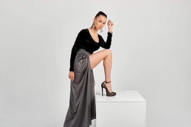 Elegante chica hermosa en un vestido gris posando en un cubo en una pared blanca