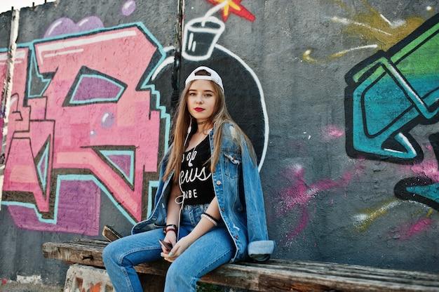 Elegante chica hipster casual en gorra y jeans usar contra la gran pared de graffiti con bomba.
