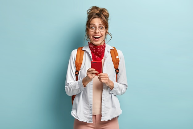 La elegante chica inconformista milenaria va a la escuela, siempre en contacto, sostiene el teléfono móvil, verifica la notificación, usa grandes gafas redondas, camisa informal y un pañuelo rojo en el cuello, lleva una mochila