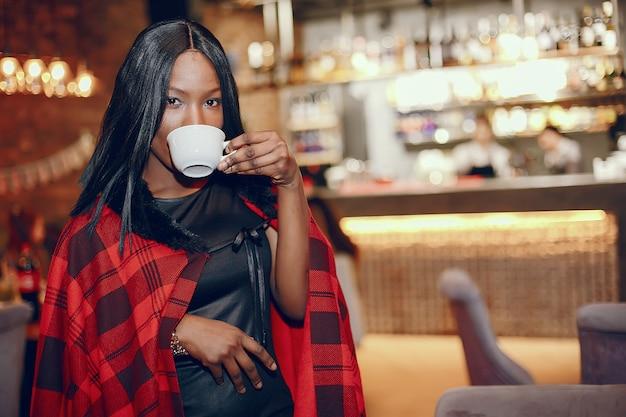 Elegante chica negra en un cafe