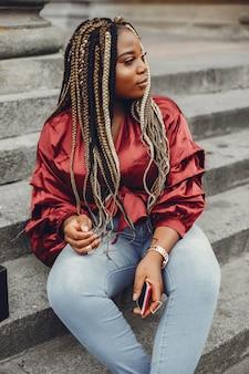 Elegante chica negra en una ciudad de verano.