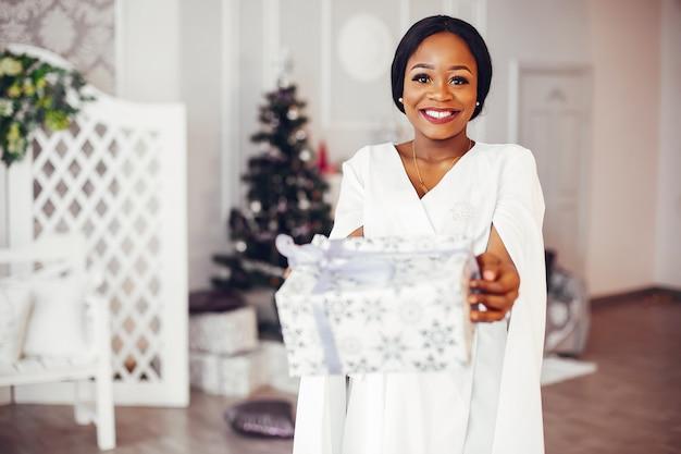 Elegante chica negra en la habitación decorada de navidad