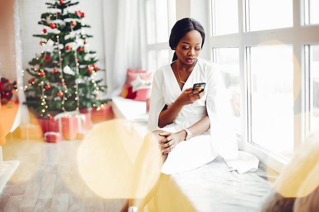 Elegante chica negra en una habitación en navidad