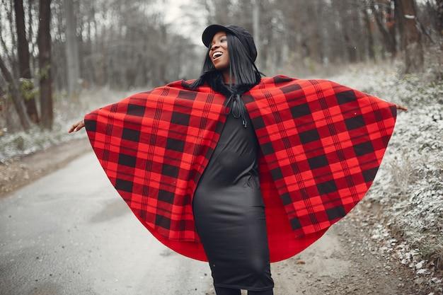 Elegante chica negra en un parque de invierno