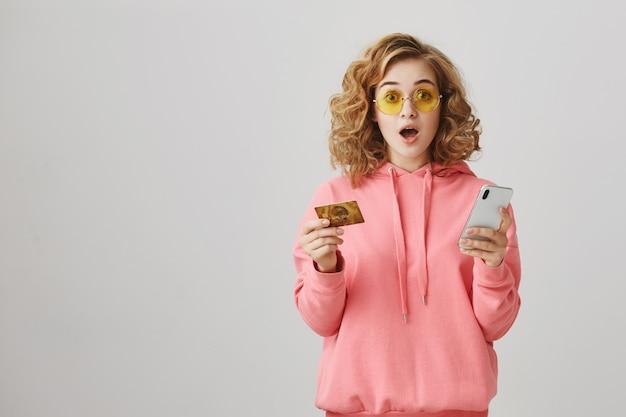 Elegante chica de pelo rizado de compras en línea, con tarjeta de crédito y teléfono inteligente