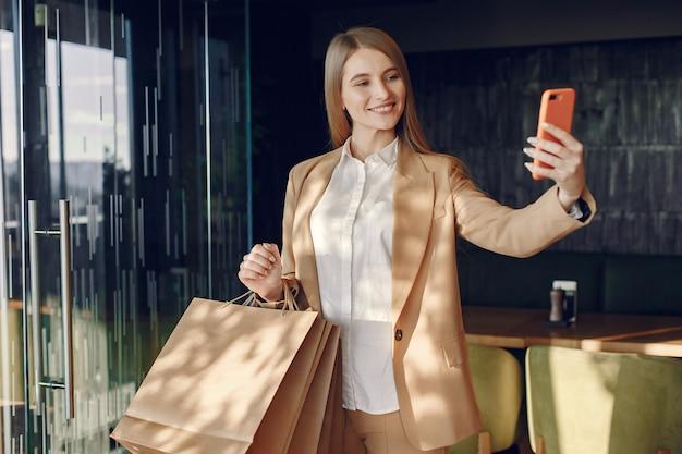 Elegante chica de pie en una cafetería con bolsas de compras