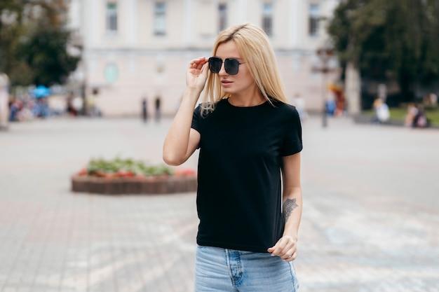 Elegante chica rubia con camiseta negra y gafas posando contra la calle