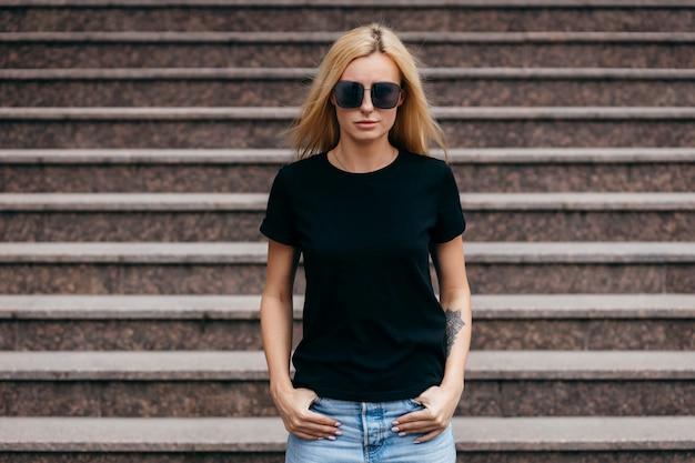 Elegante chica rubia con camiseta negra y gafas posando contra las escaleras