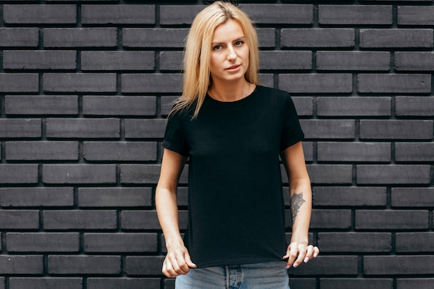 Elegante chica rubia con camiseta negra posando sobre fondo de pared negra