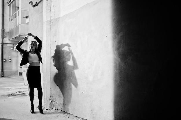 Elegante chica rubia llevar chaqueta de cuero negro posando en las calles de la ciudad, antigua muralla con sombras.