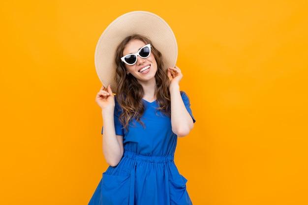 Elegante chica turista sobre un fondo naranja mirando a la cámara con una sonrisa