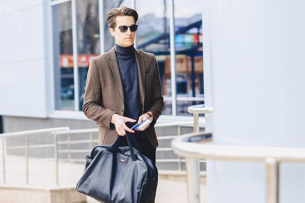 Elegante chico atractivo en chaqueta con pasaporte y entradas.