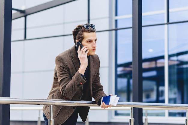 Elegante chico atractivo en chaqueta con pasaporte telefónico y entradas