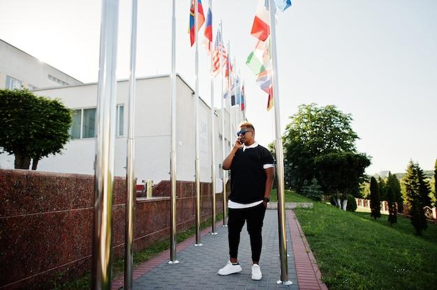 Elegante chico musulmán árabe con originalmente cabello posado en las calles, contra banderas de diferentes países.