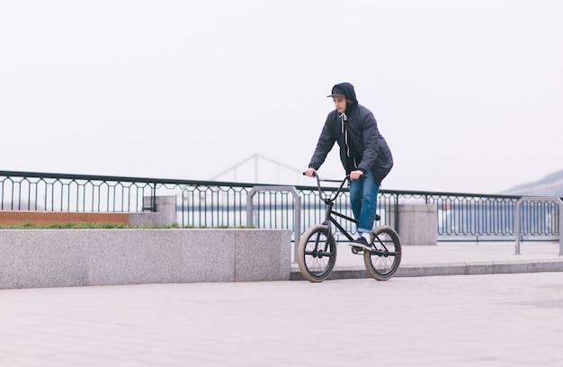 Elegante ciclista de bmx viaja a lo largo de la costa. camina en bmx en la ciudad. concepto de bmx. cultura callejera