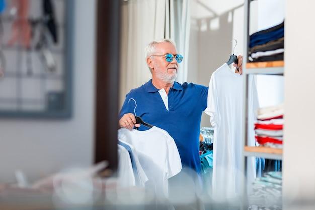 Elegante. cintura para arriba del anciano de moda con gafas de sol mientras sostiene un montón de perchas con camisetas y elige el atuendo más adecuado