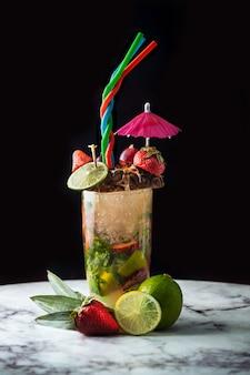 Elegante cóctel de verano con coloridas frutas y accesorios.
