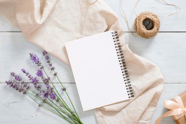 Elegante composición con flores de lavanda, bloc de notas de papel en blanco, manta de color beige pastel, cordel, caja de regalo en una rústica mesa de escritorio de madera azul