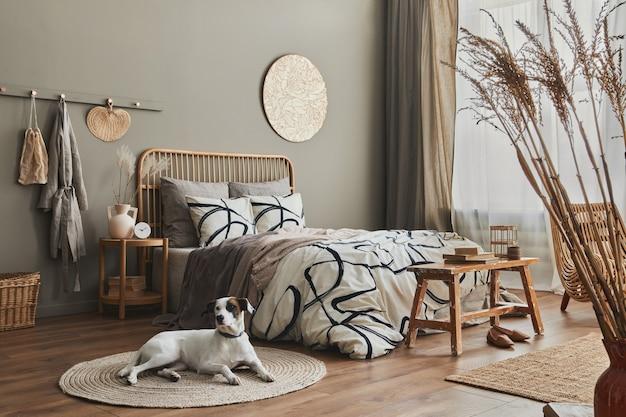Elegante composición de interior de dormitorio con cama de madera, muebles, flores secas en jarrón, decoración de ratán y elegantes accesorios. hermoso perro tirado en la alfombra.