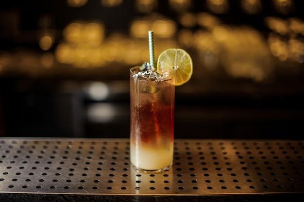 Elegante copa de cóctel con bebida fría agridulce decorada con paja y rodaja de limón