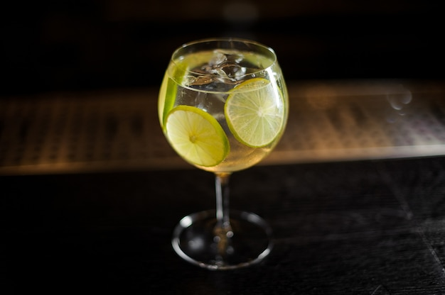 Elegante copa de cóctel con cóctel de cítricos agrios y dulces frescos con rodajas de limón en fondo oscuro