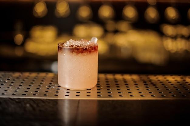 Elegante copa de cóctel llena de sabrosa bebida alcohólica dulce con hielo en la barra del bar