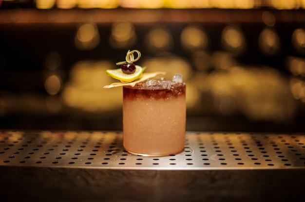 Elegante copa de cóctel llena de sabrosa bebida alcohólica dulce con hielo y rodajas de fruta en la barra del bar