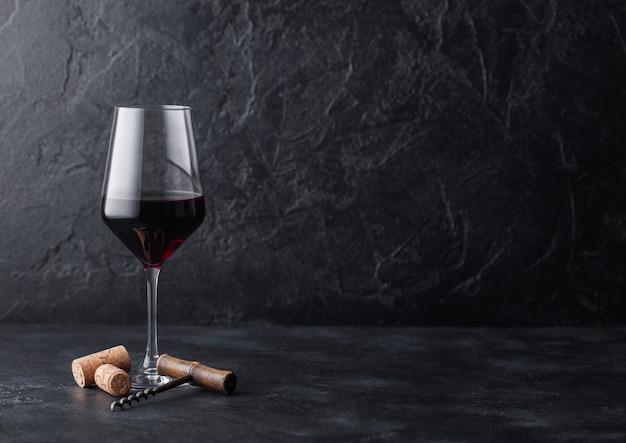 Elegante copa de vino tinto con corchos y sacacorchos sobre fondo de piedra negra.