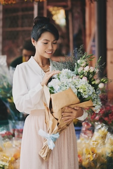 Elegante dama asiática admirando el elaborado ramo de flores frescas en la floristería