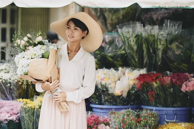 Elegante dama asiática con gran ramo esperando en la calle frente a la tienda de flores