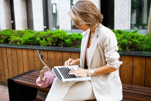 Elegante dama de negocios trabajando al aire libre con su computadora portátil