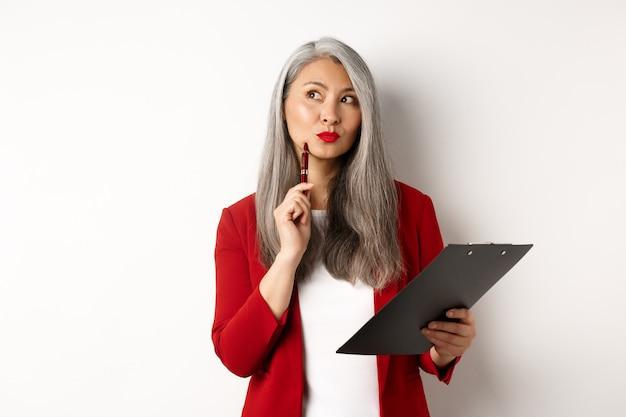 Elegante dama de oficina asiática en chaqueta roja escribiendo un informe en el portapapeles, mirando pensativo mientras trabaja, de pie sobre fondo blanco.