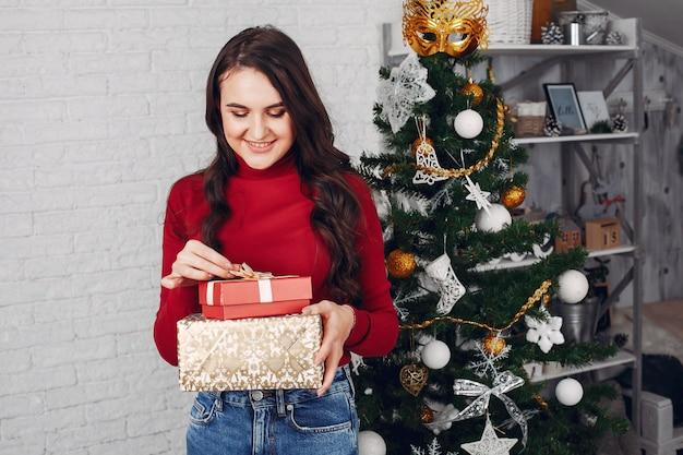 Elegante dama de pie cerca del árbol de navidad