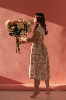 Elegante dama posando con ramo de flores