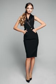 Elegante dama en vestido negro de oficina y tacones.