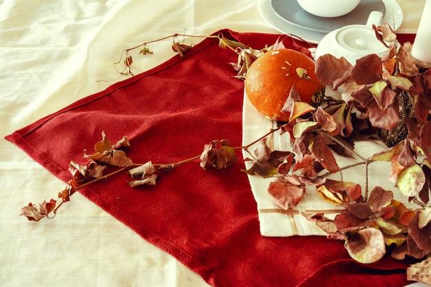 Elegante decoración de mesa de otoño de acción de gracias con calabaza y ramas secas