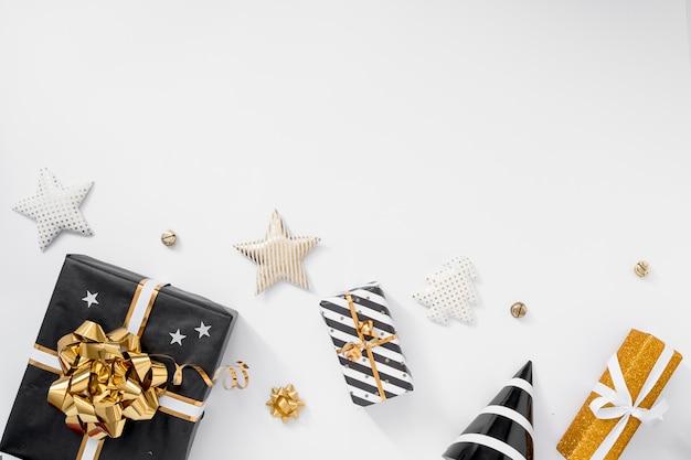 Elegante decoración navideña. regalos, sombreros, decoraciones negras y doradas sobre fondo blanco.