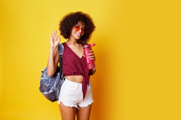 Elegante deporte mujer negra de pie sobre amarillo y sosteniendo una botella de agua rosa vistiendo elegante ropa de verano y mochila.