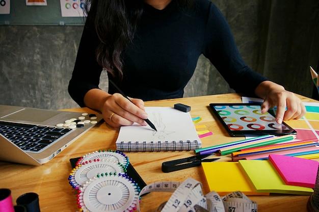 Elegante diseñador de moda de trabajo como boceto de la nueva colección en el taller. concepto de diseño creativo