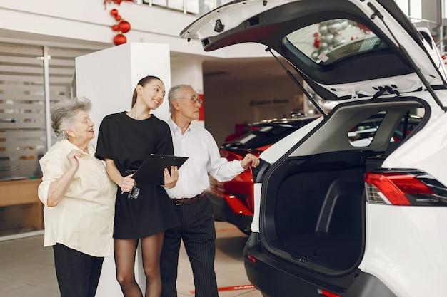 Elegante y elegante pareja de ancianos en un salón del automóvil