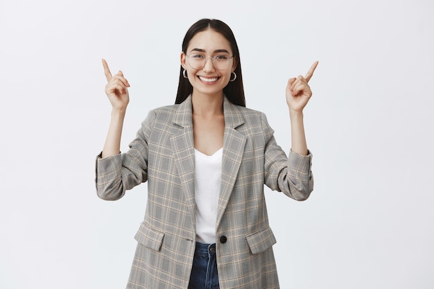 Elegante empresaria adulta optimista con gafas y chaqueta de moda, levantando las manos y apuntando hacia arriba mientras sonríe ampliamente