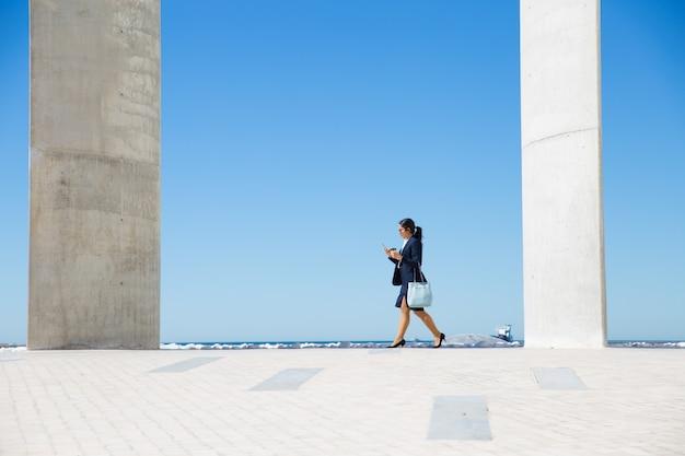Elegante empresaria caminando por el paseo marítimo