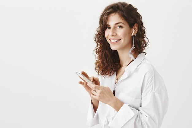 Elegante empresaria exitosa con teléfono móvil y auriculares inalámbricos