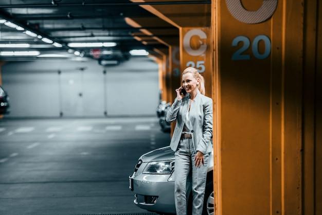 Elegante empresaria hablando por teléfono móvil en el aparcamiento subterráneo.