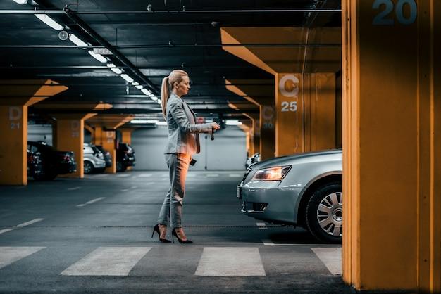 Elegante empresaria con las llaves del auto frente a un auto en un estacionamiento subterráneo.