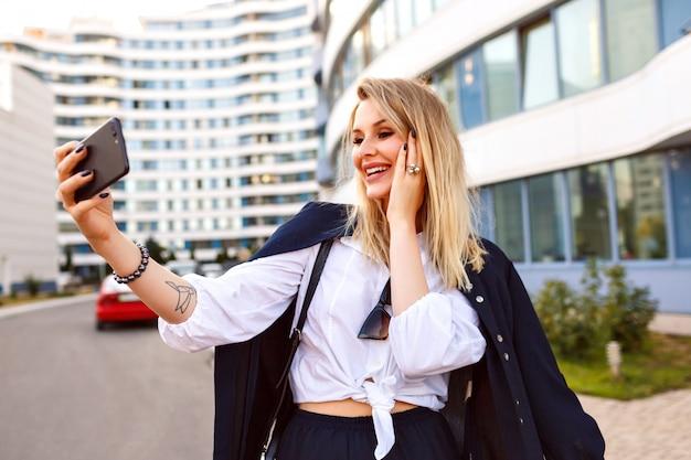 Elegante empresaria posando en la calle cerca de la oficina, vestida con traje elegante y moderno y bolso de cuero, pelos rubios haciendo selfie y sonriendo, hablando por video chat.