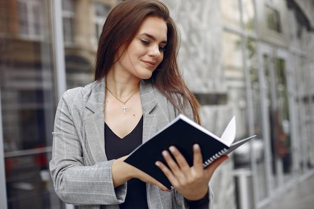 Elegante empresaria que trabaja en una ciudad y usa el cuaderno